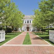 Granite, brick pavers and a double row of honey locust trees inside a white-painted swinging gate create a symmetrical approach to the large house. Lawn, flowers and hedges soften the formality of the space.