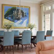 Soft colors and vibrant art spill into the dining end of the room.