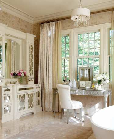 The haute master bath includes a dainty chair upholstered in snowy terry cloth.
