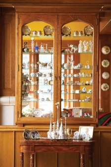 A see-through curio cabinet separates the mudroom and kitchen.