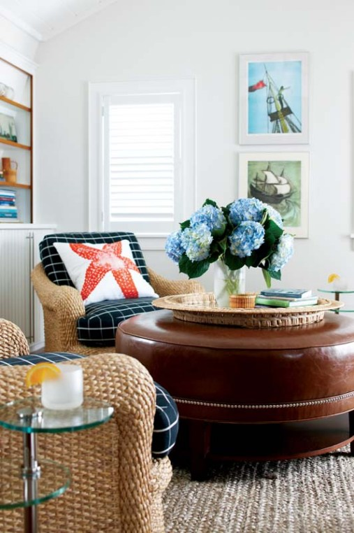 """A custom, round faux-leather ottoman takes center stage in the living room; designer Kathleen Hay added polished-nickel nailhead trim """"for a bit of sparkle and shine."""""""