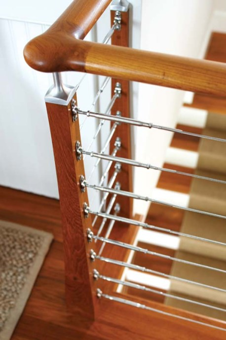 The nautical-inspired teak staircase has horizontal, stainless-steel cable balustrades.
