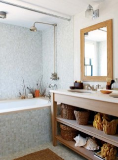 The master bath has gray-green glass mosaic tiles and driftwood-finished vanities.