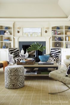 A creamy coat of paint took built-ins from dark to airy in the media room. Animal prints and contemporary art bring a modern flair.