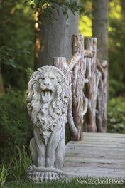 Repurposed stone lions flank a rustic footbridge.