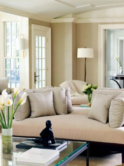 """The living room's custom """"see-through"""" mahogany and velvet sofa unites two of the room'€™s three seating arrangements."""