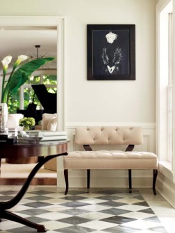 The foyer'€™s antique marble makes a dramatic statement beneath a contemporary velvet settee.