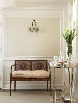 An antique sconce is a grace note above a cane-backed settee.