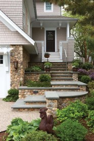 Stone steps lead to the front door, which opens to the home's second level.