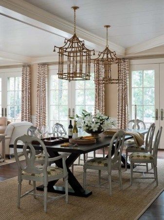 Twin iron lanterns painted to look like bamboo hang above a Holly Hunt dining table.