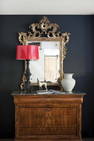The streamlined decor includes the occasional antique piece such as the armchair and a gilded mirror atop marble-topped chest in the living room.