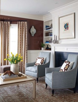 Texture plays a large role in the living room, where walls are treated to a glossy chocolate-brown lacquer, chairs and sofa wear cushy fabrics and the rug is woven in a high-low geometric in wool and linen.