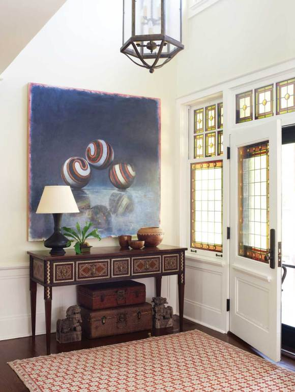 Designer Fotene Demoulas enhanced the gracious foyer by adding a rug and sideboard with mosaic patterns.