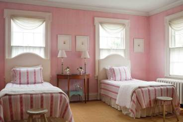 A range of pinks brings a rosy glow to a guest room.