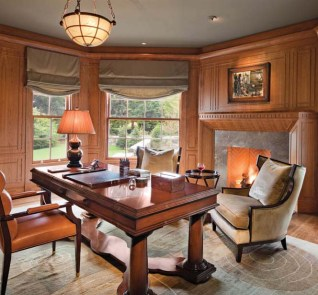 An office paneled in rich cherry includes a Rumford fireplace