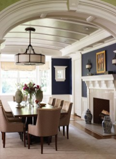 Deep blue walls and a barrel-vaulted ceiling with shimmering silver paint bring drama to the dining room.