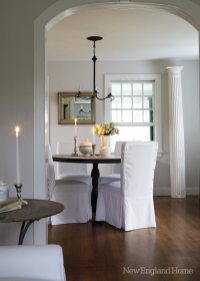 Chairs in prim slipcovers surround the dining room's zinc-topped table.