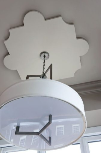 The dining-area light fixture hangs from a medallion the designers created.