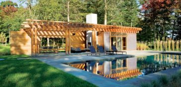 The pool house is a contemporary interpretation of the timber-frame main house