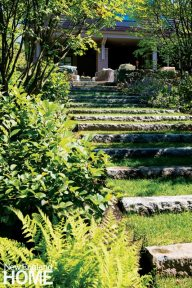 Old granite curbstones create a casual staircase from the patio to the lower yard.