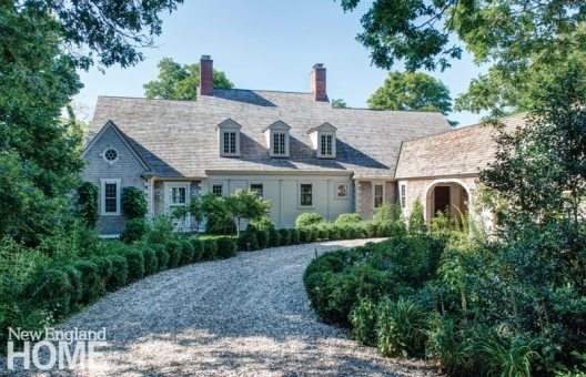 """A crushed-clamshell drive lined with boxwood leads to the new porte-cochère. The home's top-to-bottom update blends modern features and character-infusing details, such as high-efficiency windows made with hand-blown glass. """"A typical summer house has become a four-season home,"""" says interior designer Helen Higgins."""