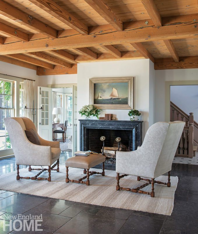 cape cod style house living room decoration in ghana and sustainability on new england home magazine louis xiii wing chairs a leather upholstered ottoman help create comfortable fireside oasis the great sustainable