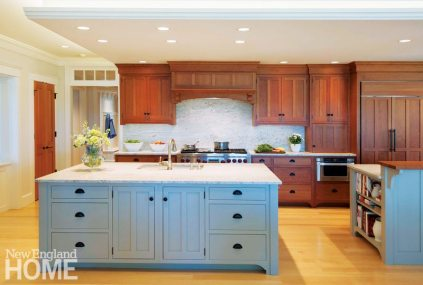 This kitchen by Crown Point Cabinetry features a maple island, painted a soft blue, surrounded by perimeter cabinets in a rich cherry finish.