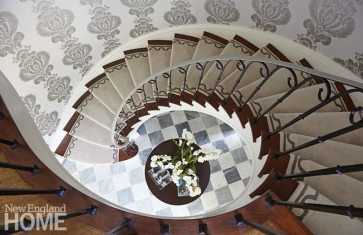 The eye-catching staircase, original to the 1930s home, spirals down to a custom, walnut-stained figured-sapele table.