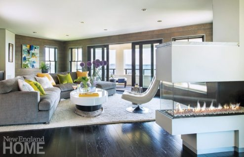 The apartment's open floor plan allows light to spill in from the patio on the west end of the carriage house. Urban contemporary furnishings against shiplap walls are a nod to both city and sea.