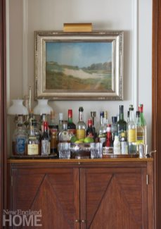 The owners collect landscape paintings, like this nineteenth-century watercolor by Sydney Yard that hangs above the great room bar.