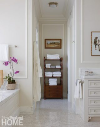 Applied wall moldings pair with Carrara marble in the master bath, instilling an air of bygone elegance.