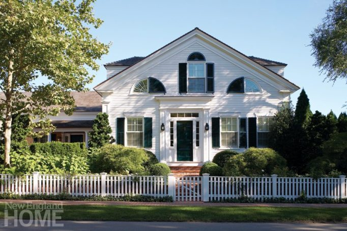 The Greek Revival house retains its asymmetrical facade and clapboard face, but was raised three feet and paired with a new bedroom wing, at left. A terraced front yard hides the elevation change, while the classic picket fence disguises the retaining wall behind it.