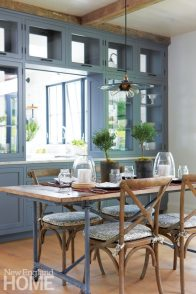 With a zinc base and an antique elm door for a top, the dining table fits right into the materials palette; a pass-through connects to the kitchen.