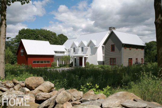Reading as several interconnected structures, the house rests behind a stone wall that separates two meadows on the property, once part of a working farm. Hidden from sight is a 20-kilowatt solar array that produces much of the home's electricity.