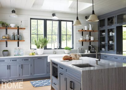 The kitchen's shiplap walls, wooden shelves, and traditional-style lighting preserve a sense of rusticity that is playfully challenged by the island's waterfall edge and contemporary faucet.