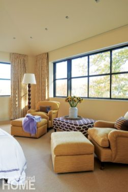 The master suite's yellow curtains and George Smith chairs match the headboard as well as the fall colors outside. The throws and ottoman are in shades of client-pleasing purple.