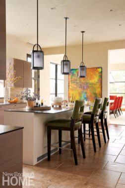 Pretty things come in threes in the custom kitchen, where a trio of A. Rudin high-backed stools in faux leather line a concrete-topped counter lit by bronze pendant lights.
