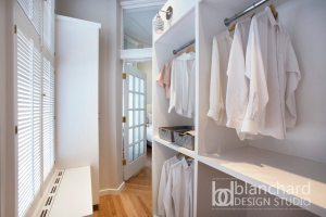 Underutilized space was given new life as a luxurious custom closet. The tall cabinet on the left hosts a jewelry cabinet built with locks for security.