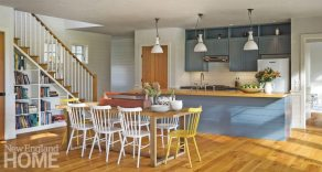 The open-plan kitchen is set off from the rest of the first floor by bold colors on the cabinets and island, as well as a pair of bright yellow dining chairs.