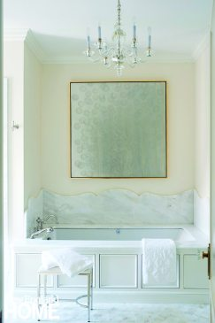 Silver-leaf artwork, a glass chandelier, and a Calacatta marble tub ratchet up the luxe factor in the master bath.