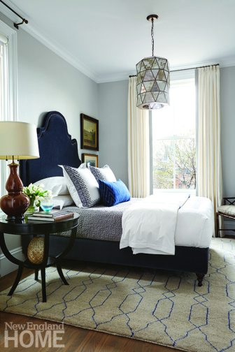 The master bedroom is quietly sophisticated, with neutrals leaning more toward gray. Its showstopper is the stunning Ingrid bed with velvet headboard from Oly Studio, enhanced by embroidered John Robshaw bedding. A mirrored light fixture adds a touch of drama.