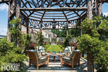 Bluestone pavers around an antique millstone set beneath the table elevate the serene gazebo, which is shaded by wisteria sinensis.