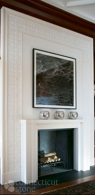 Chesney fireplace mantel with custom limestone moldings and decorative plaster tile