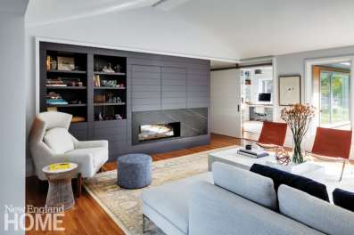 Modern furnishings and shiplap cabinetry are in keeping with the architecture of the house.