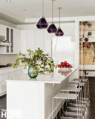 Amethyst blown-glass pendants hanging above the island lend a nice touch of color to the high-gloss white kitchen.