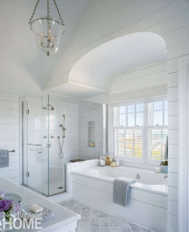 The master bath is made for relaxation, with its tub tucked beneath a decorative arch and next to a broad window with stellar views.
