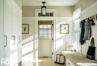 Like the rest of the house, the mudroom paneling is painted a bright white that helps fill the home with light.