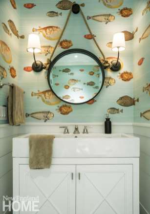 The ocean-inspired first-floor powder room features woven wallpaper with gaily painted fish and a circular mirror hung by a sturdy rope.