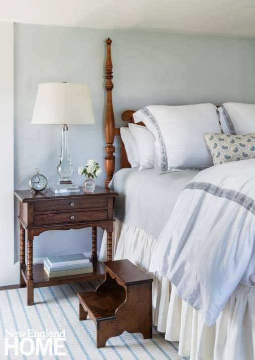 """With its mild blues and grays, warm wood, and a traditional step-up, four-poster bed, the master bedroom conveys what designer Susanne Lichten Csongor calls """"a sense of incredible comfort."""""""