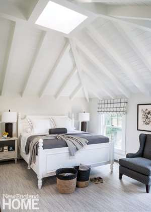 Simple, white-painted furniture in the second-floor guest bedroom comports with the owners' desire for cottage decor in this space.